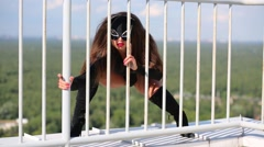 Woman Cat in black costume poses behind railing on roof Stock Footage