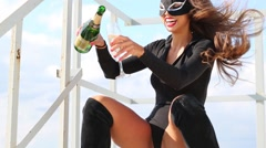 Woman Cat in black costume laughs and pours wine on roof Stock Footage