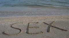 sex handwritten in sand on a beach - stock footage