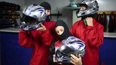 Woman, boy and girl in balaclavas wear helmets in leisure club Stock Footage