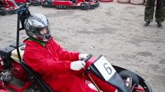 Boy in helmet in small kart rides on track. Text on blue: start Stock Footage