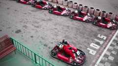 Two riders in helmets finish in small karts on grey track outdoor Stock Footage