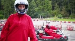 Woman in helmet and moving karts on track out of focus Stock Footage
