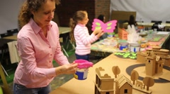 Happy woman and girl paint cardboard crafts on table Stock Footage
