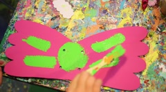 Close up of hands painting bright cardboard wings above table Stock Footage