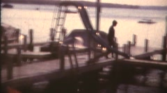 Silhouette father and son on dock. 8mm Vintage Stock Footage