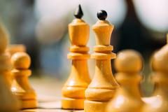 Old Chess Standing On Chessboard - stock photo
