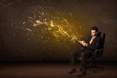 Stock Photo of Businessman with tablet and energy explosion on background