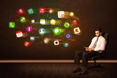 Business man sitting in office chair with tablet and colorful app icons Stock Photos