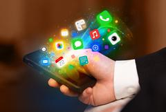 Hand holding smartphone with colorful app icons - stock photo