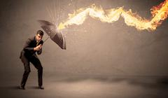 Business man defending himself from a fire arrow with an umbrella Stock Photos