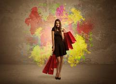 Girl with shopping bags and paint splatter - stock photo