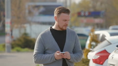 The young man goes on the parking and thumbs through a news feed on the Internet - stock footage