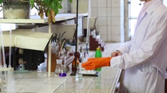Male hands in orange gloves take flask with transparent liquid in lab Stock Footage