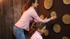 Mother and girl play with sticks and wooden wheels on wall Stock Footage