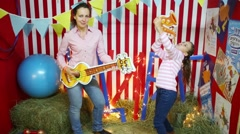 Woman and girl with cardboard sax and guitar in Cardboard town Stock Footage