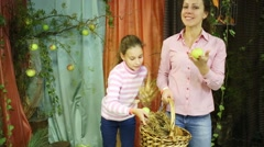 Happy mother and daughter put apples and ears to basket Stock Footage