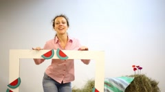 Happy woman poses in big frame with watermelon among hay indoor Stock Footage
