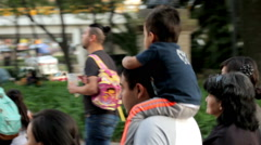 A father holds in his shoulders his son while they walk in the park. Stock Footage