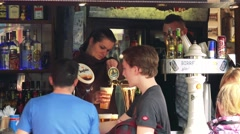 Two young man in front of stand with refreshments where woman draw a beer - stock footage