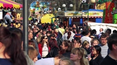 People walk and observe stands with refreshment and attraction in funfair - stock footage