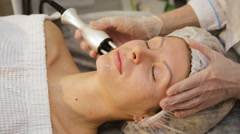 Young woman receiving electric facial massage Stock Footage