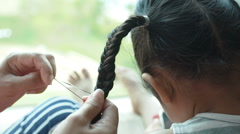 Woman hand making braid for little girl. Stock Footage