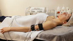 Woman with electro stimulator electrodes on her body - stock footage