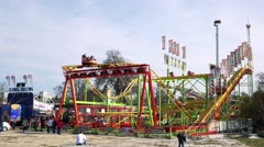 Fairground attractions with people in funfair Stock Footage