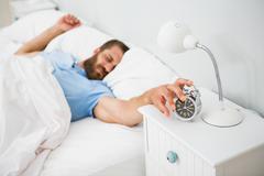 Sleeping man awakened by a alarm on bed Stock Photos