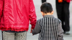 Mother holds his hand to his son while they walk in the park. Stock Footage