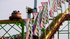 People sit in seats on attraction in height-under them people ride on atrraction Stock Footage