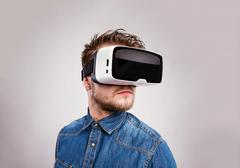 Man wearing virtual reality goggles. Studio shot, gray backgrou - stock photo