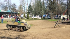 Stock Video Footage of People ride on small army tanks in park on sand