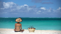 Sexy hat bikini woman tanning relaxing on beach Stock Footage