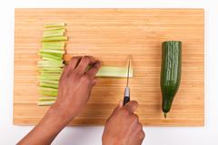 African  American womans hand slicing cucumber - Flat lay - stock photo