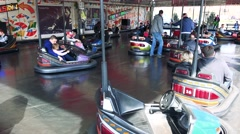 People get in to small runabout on track in funfair Stock Footage