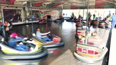 People sit in seats in small runabout on track and ride in funfair Stock Footage