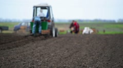 Agricultural tractor plows soil and plantings of agricultural cultures, blurred Stock Footage