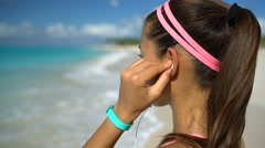 Runner Listening To Music Running Exercising On Beach Putting Headhones in ear Stock Footage