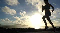 Running silhouette of woman runner working out at beach sunset - stock footage