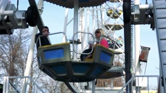 People sit in swing seats on ferris wheel and slowly turn around Stock Footage