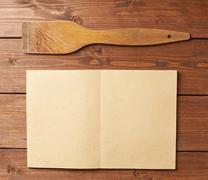 Wooden spatula next to empty sheet - stock photo