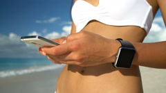 Smartwatch And Smart Phone On Beach - Woman In Bikini Using Wearable Tech Stock Footage