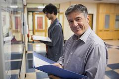 Portrait of smiling professor standing in front of notice board - stock photo