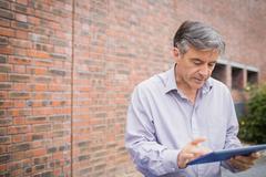 Professor using digital tablet in campus Kuvituskuvat