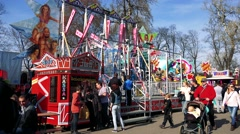 People walk and observe attraction and stands in funfair - stock footage