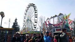 Big ferris wheel and other attraction turn in funfair where people walk Arkistovideo