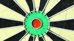 A dart strikes the bulls-eye of a dartboard. macro  - stock footage