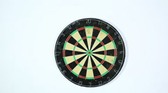 A dart strikes the bulls-eye of a dartboard. Wide shot of a dart board from belo - stock footage